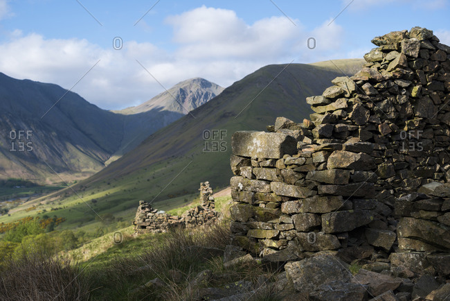 Crumbling stone houses in the English Lake District in Wast Water with views of Kirk Fell and Great Gable in the distance