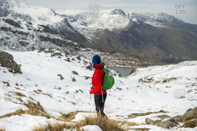 Hiking in the snow towards the top of Tryfan looking towards the Glyder mountain range in the distance and Llyn Idwal below