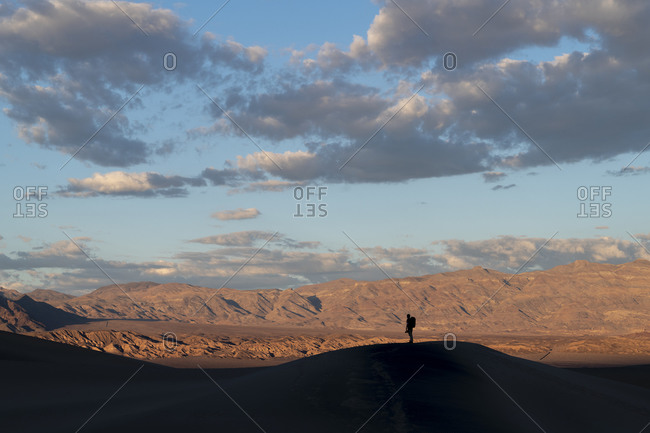 A photographer stands silhouetted on top of one of the Mesquite Flat Sand Dunes backed by mountains
