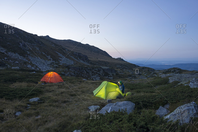Tents glow in the twilight beside one of the Maliovitsa lakes in the Rila mountains