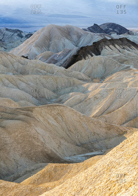 Eroded gulleys through different colored layers of rock caused by erosion make surreal rock formations near Zabriske Point