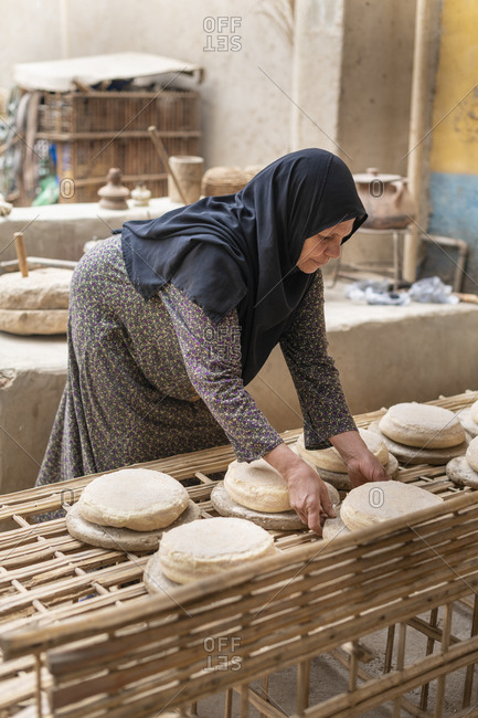 An Egyptian woman wearing traditional clothes working in a small bakery making traditional bread