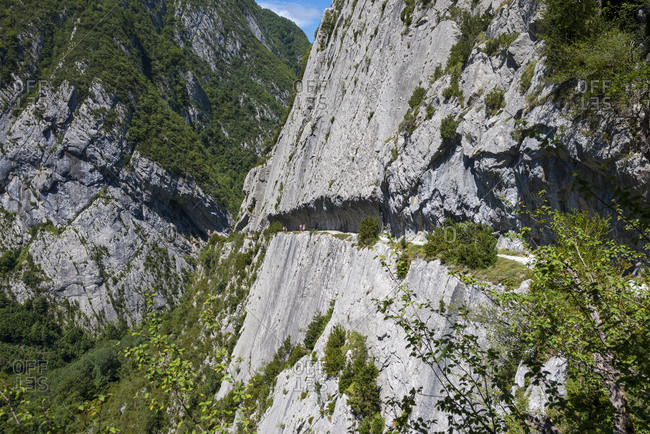 Walkers make their way along the Chemin de la Mature a 1200m path carved into a sheer rock face and part of the GR10 long distance footpath