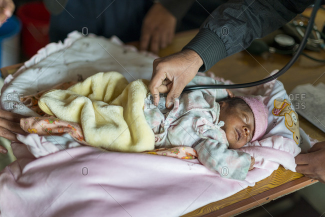 A doctor checks a baby in a hospital in Nepal