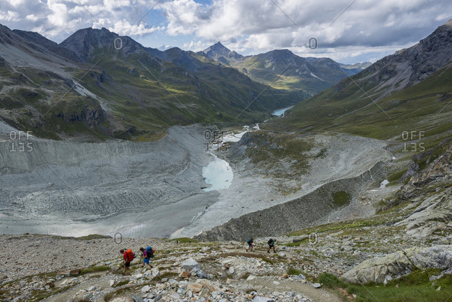 Moiry glacier, Valais, Switzerland - August 14, 2017: hikers beside the Moiry glacier on the Walkers Haute Route from Chamonix to Zermatt