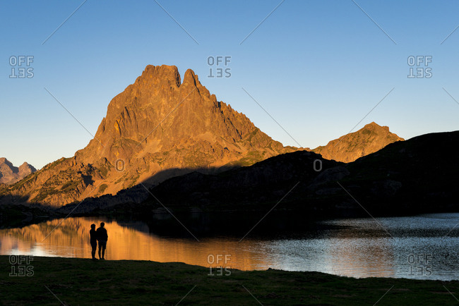 Walkers watch the sunset on Pic Midi d'Ossau beyond Lac Gentau beside the GR10 trekking route