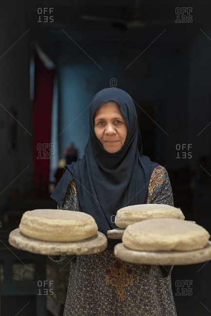 An Egyptian woman wearing traditional clothes holds some freshly baked loaves of bread outside her small bakery at home