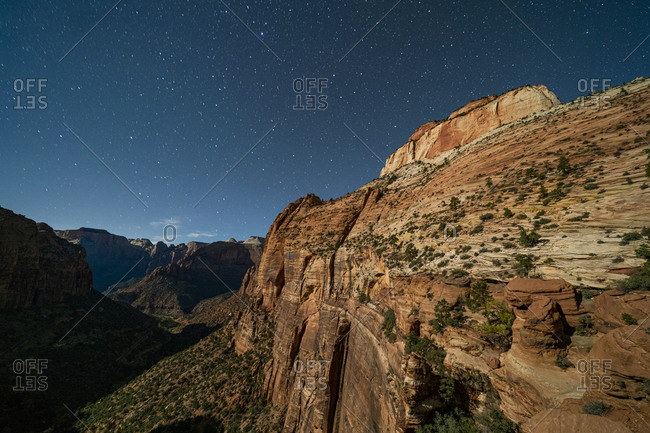 Star filled time sky over Zion Canyon National Park with car headlights making light trails