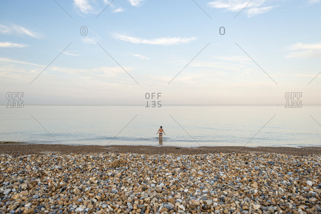 A woman goes for a swim in calm water at Sandwich Bay in Kent