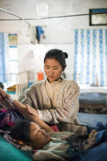 Okhaldhunga Hospital, Nepal - December 11, 2015: Paralysed woman with her neck in Gardener Wells tongs traction in a basic hospital in Nepal. Daughter is helping with physical therapy.