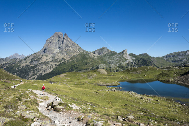 Pyrenees, , Pyrenees Atlantiques, France - July 27, 2017: A panoramic view of Lac du Miey and Pic Midi d'Ossau and the GR10 hiking trail leading off into the distance