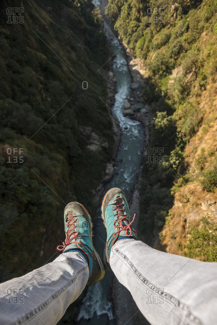 Dangling feet from a high bridge near The Last Resort in Nepal