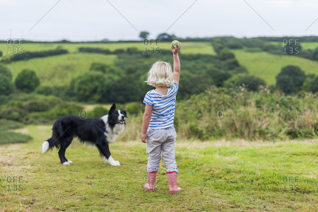 Penzance, Cornwall, UK - September 1b, 2004: A little girl throws a ball for a Border Collie dog
