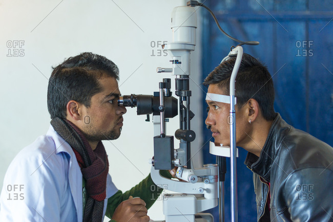 A optician or optometrist tests a patients eyesight in a small hospital in Nepal