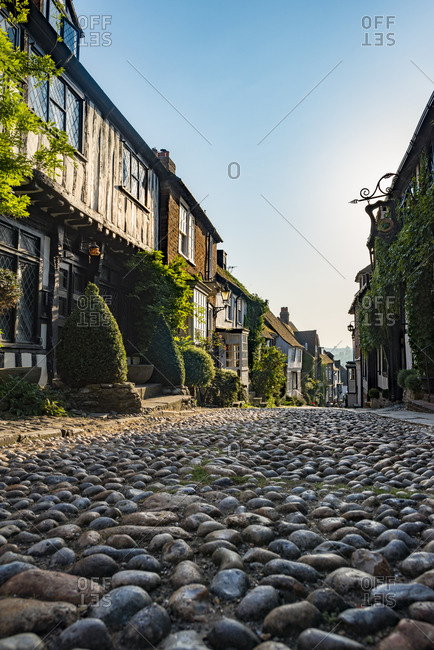 Mermaid Street in the historical little town of Rye in East Sussex in the UK. The cobbled lane is lined with medieval, half-timbered houses.