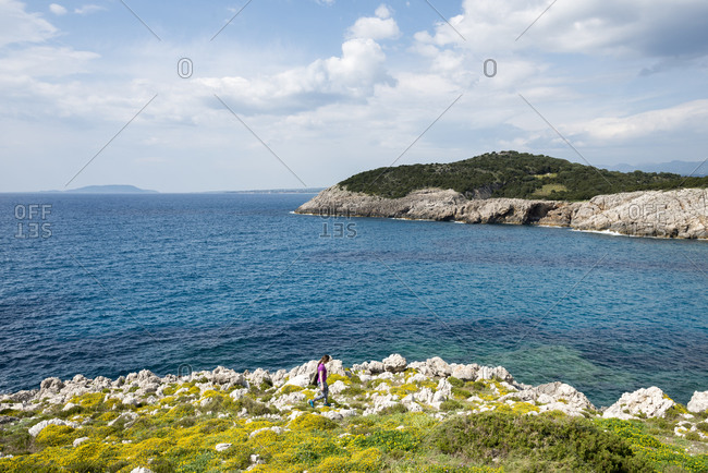 A woman explores the headland near Voidokilia beach in the Peloponnese in Greece