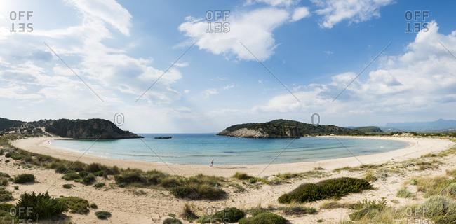 A woman walks along Voidokilia beach in the Peloponnese in Greece