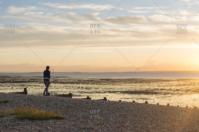 Woman standing at the waters edge of the beach at Whitstable