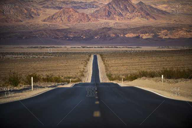 Highway through Death Valley with mountains in the distance