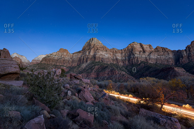 The typical steep red cliffs of Zion National Park glow in the moonlight as car headlights passing through leave light trails