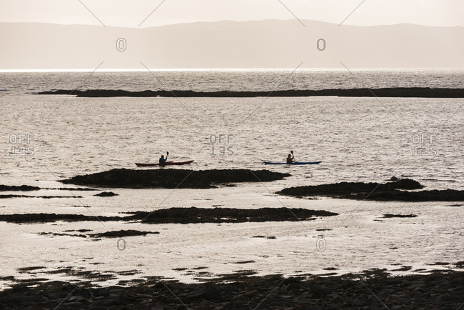 Canoeists paddle in Applecross Bay in Scotland with views of the isle of Raasay in the distance