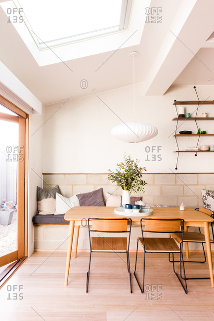Dining room with wooden table and bench made from concrete blocks and pillows under large skylight window