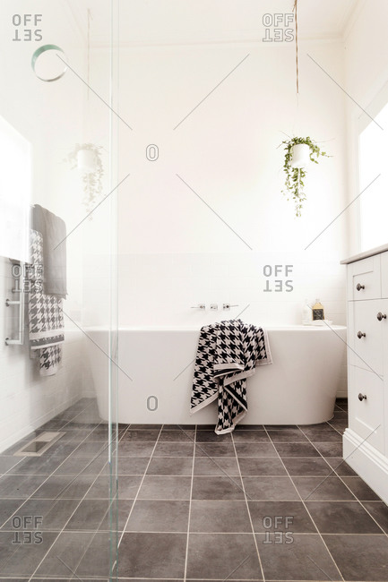Soaker tub in a bright modern bathroom with gray tile floor