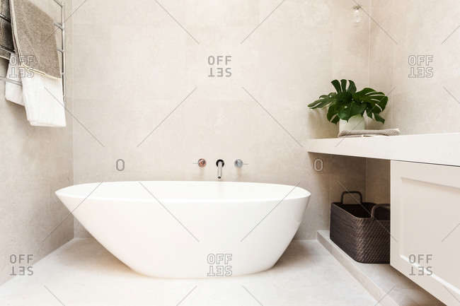 Modern soaker tub in a bright bathroom with light gray tile