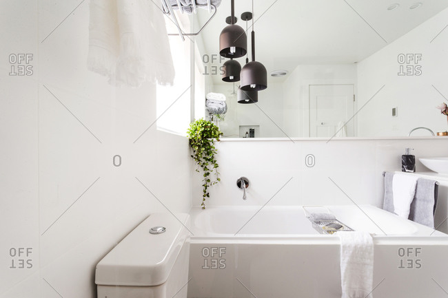 Modern bathroom with bathtub under large mirror and rubbed oil bronze pendant lights