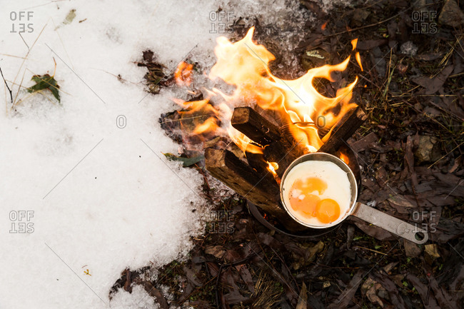 Campfire in the snow with a pan cooking fresh eggs