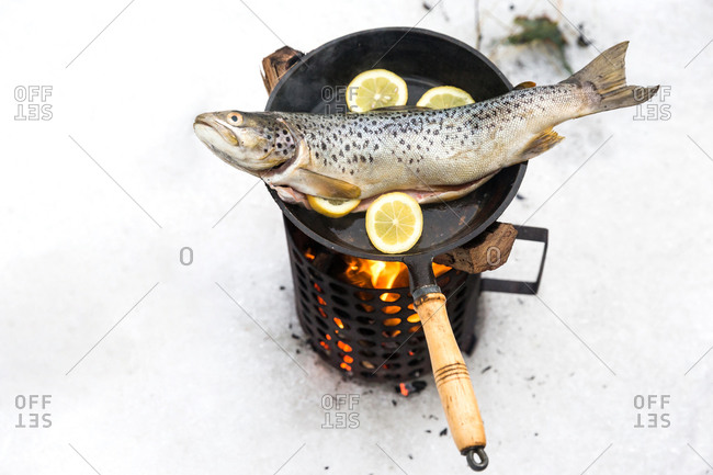 Fish being prepared in a frying pan in the snow over fire