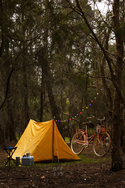 Yellow tent with strand of colorful lights attached to tree beside retro pink cruiser bike