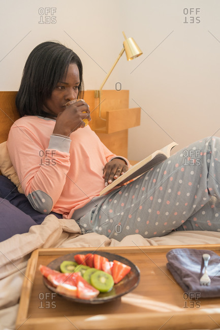 African American woman reading a book in her bed and sipping juice as part of a healthy breakfast