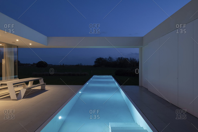 November 12, 2020: Infinity swimming pool outside of a modern home at night