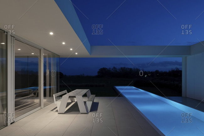 November 12, 2020: Patio with table and infinity swimming pool outside of a modern home at night