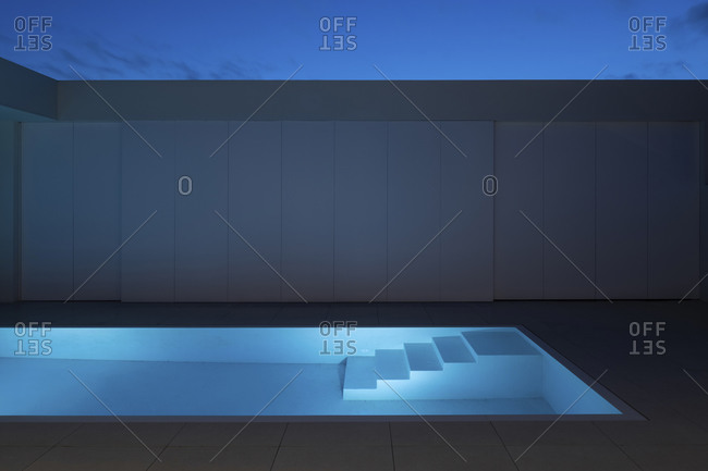 November 12, 2020: Illuminated infinity swimming pool outside of a modern home at night