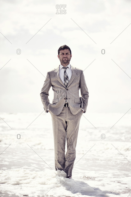 Serious man in a suit standing in the ocean