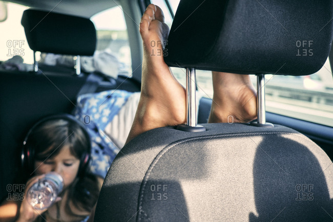 Girl relaxing in the back of a car with her feet up
