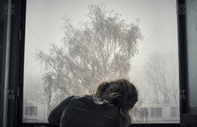 Young girl looking outside at the fog in a dreamy way