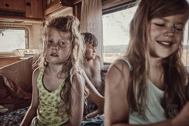 Three children in the back of a camper on holiday on a hot summers day