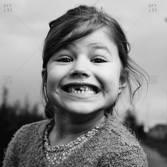 Girl showing her lost front tooth with great pride