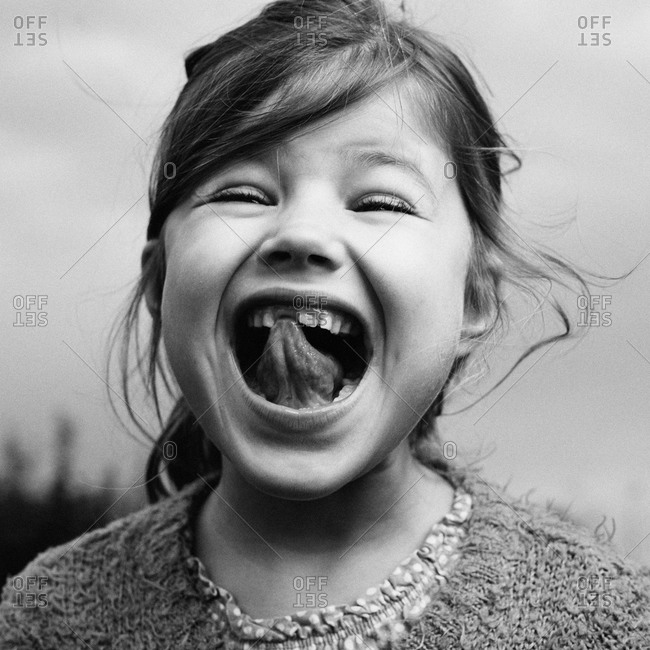 Girl showing her lost front tooth and touching her tongue to the open spot