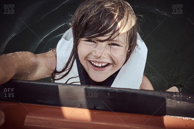 A young girl clinging to the side of a boat in her life vest full of laughter