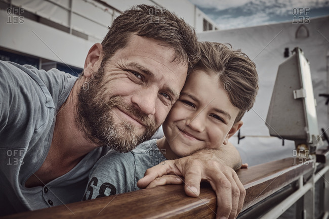 Father and son together on the railing of a boat