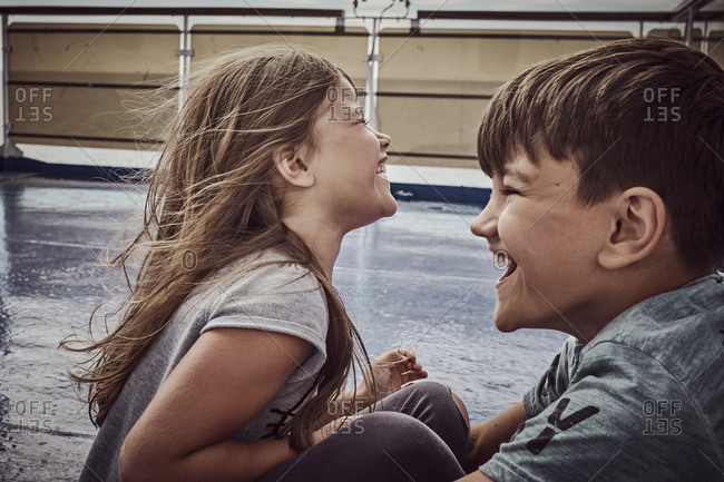 A boy and a girl on a boat laughing together
