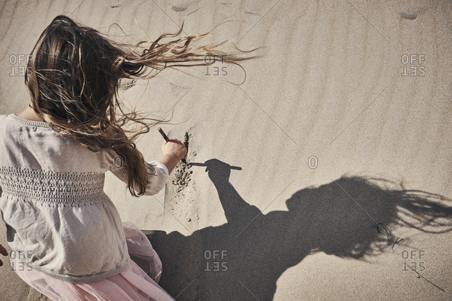 Girl drawing in the sand in the dunes on a sunny day