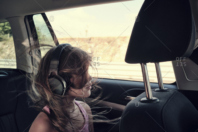 A young girl listening to music in the back of a car through her head phones