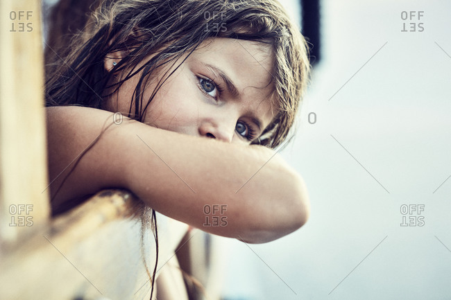 Young girl overlooking boat railing and dreaming on the sea