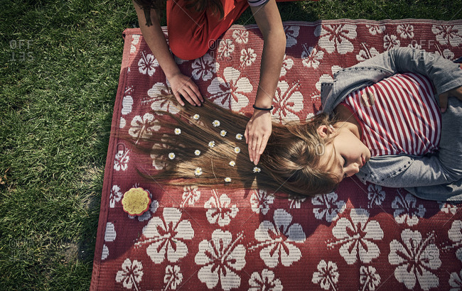 Overhead view of a you girl decoration her friend with flowers in her long hair as she lies on a blanket