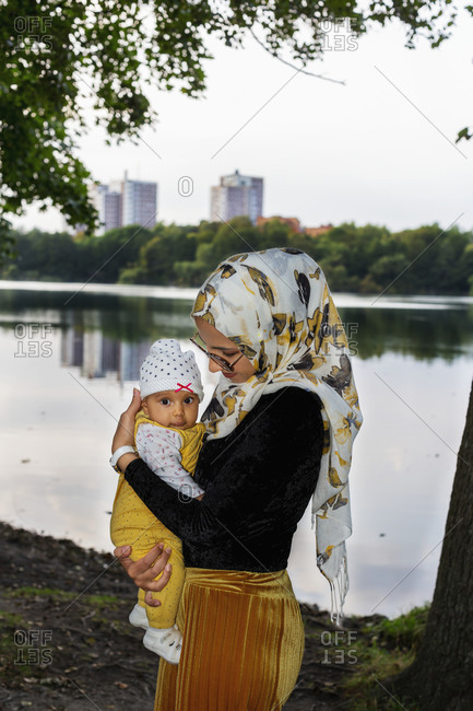 Mother carrying baby daughter - Offset Collection